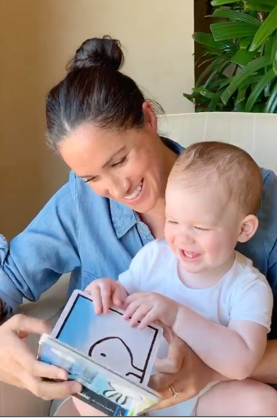 """In this photo taken by Prince Harry, Duchess Meghan of Sussex reads """"Duck! Rabbit!"""" to their son Archie who celebrated his first birthday May 6, 2020, in Los Angeles. She is wearing a chambray shirt."""