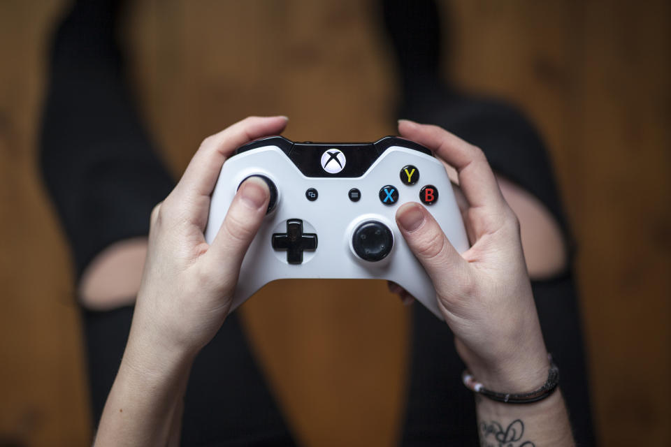 Gothenburg, Sweden - January 17, 2015: A shot from above of a young woman's hands holding a white Xbox One controller as she is playing a video game. Natural lighting, shot on wooden background with shallow depth of field.