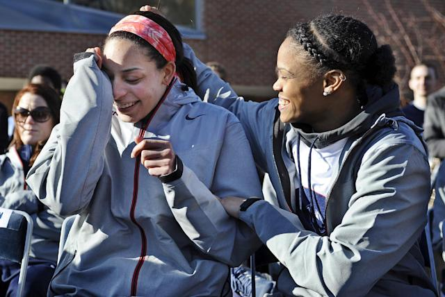 Connecticut's Moriah Jefferson, right, reaches over to comfort teammate Bria Hartley after Hartley became emotional during a speech to fans arriving at a rally on campus celebrating Connecticut's NCAA women's college basketball title, Wednesday, April 9, 2014, in Storrs, Conn. (AP Photo/Jessica Hill)
