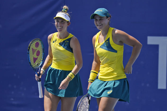 The Australian doubles team of Ashleigh Barty, right, and Storm Sanders talk during the quarterfinals of the tennis competition at the 2020 Summer Olympics, Wednesday, July 28, 2021, in Tokyo, Japan. (AP Photo/Seth Wenig)