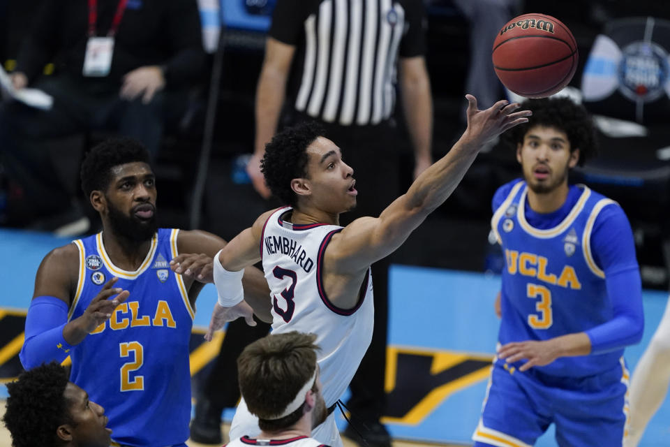 Gonzaga guard Andrew Nembhard, center, drives to the basket between UCLA forward Cody Riley, left, and guard Johnny Juzang, right, during the first half of a men's Final Four NCAA college basketball tournament semifinal game, Saturday, April 3, 2021, at Lucas Oil Stadium in Indianapolis. (AP Photo/Darron Cummings)
