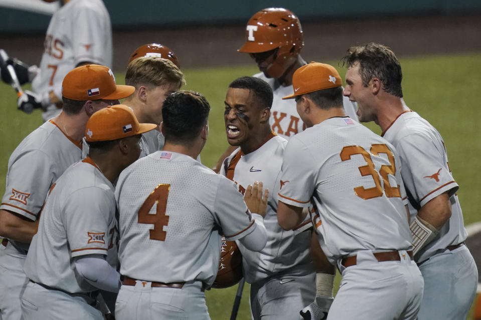 Texas' Camryn Williams, center, celebrates a two-run homer against South Florida during the seventh inning of an NCAA Super Regional college baseball game, Sunday, June 13, 2021, in Austin, Texas. (AP Photo/Eric Gay)