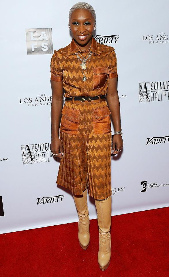 in a Missoni orange chevron belted short-sleeve jumpsuit, with tan leather knee-high boots at the 4th Annual Oscar Nominee reception in Hollywood.