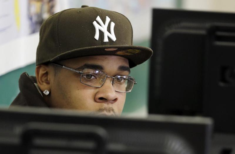 In this Tuesday, Feb. 5, 2013, file photo, Student Demarcus Miller listens to a teacher from behind a computer terminal in a GED preparation class in Buffalo, N.Y., Tuesday, Feb. 5, 2013. Adults who've begun working toward their GED are being urged to finish up this year, before the test for a high school equivalency diploma changes and they have to start all over. (AP Photo/David Duprey)