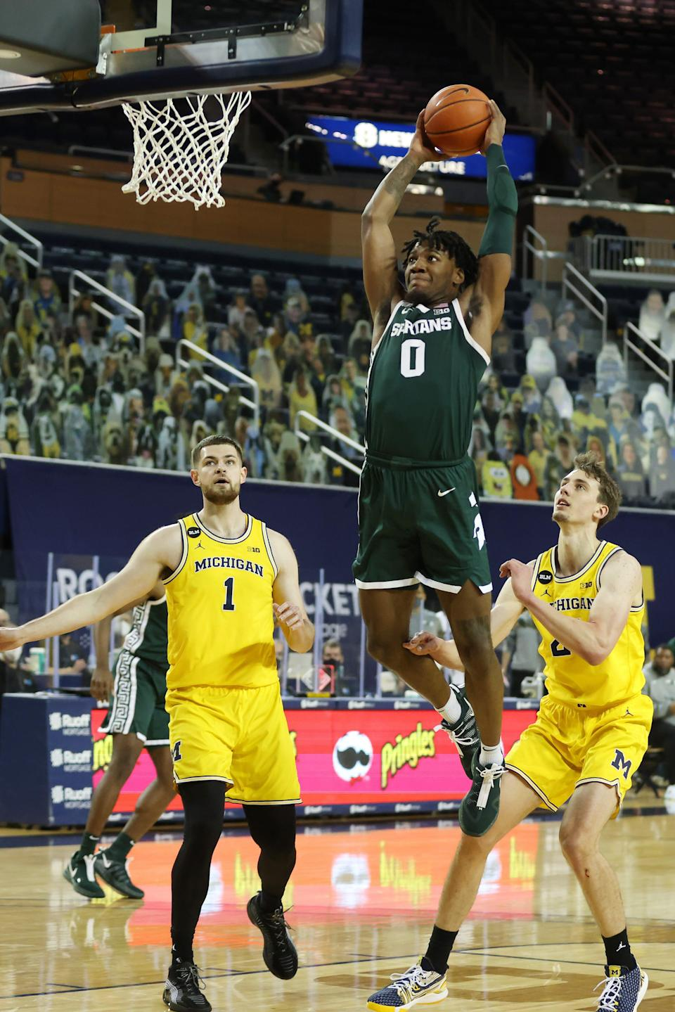 Michigan State's Aaron Henry dunks past Michigan's Hunter Dickinson (1) and Franz Wagner (21) during the first half at Crisler Center on March 4, 2021 in Ann Arbor.