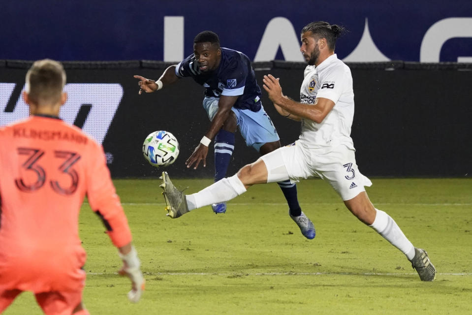Vancouver Whitecaps's Cristian Dajome, center, takes a shot on goal as Los Angeles Galaxy's Emiliano Insua (3) defends during the second half of an MLS soccer match, Sunday, Oct. 18, 2020, in Carson, Calif. (AP Photo/Marcio Jose Sanchez)