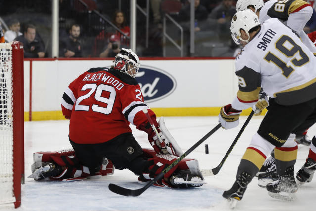 New Jersey Devils goaltender Mackenzie Blackwood (29) blocks a shot with Vegas Golden Knights right wing Reilly Smith (19) and Golden Knights right wing Alex Tuch (89) in front of the crease during the first period of an NHL hockey game, Tuesday, Dec. 3, 2019, in Newark, N.J. (AP Photo/Kathy Willens)