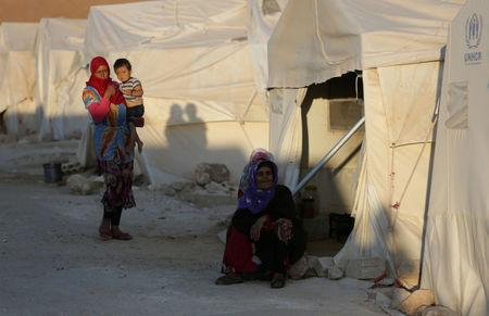 FILE PHOTO: An internally displaced woman sits outside a tent in Idlib province