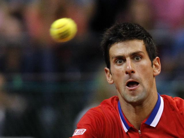Novak Djokovic of Serbia returns a ball to Milos Raonic of Canada during their Davis Cup semifinal tennis match in Belgrade, Serbia, Sunday, Sept. 15, 2013. (AP Photo/Darko Vojinovic)
