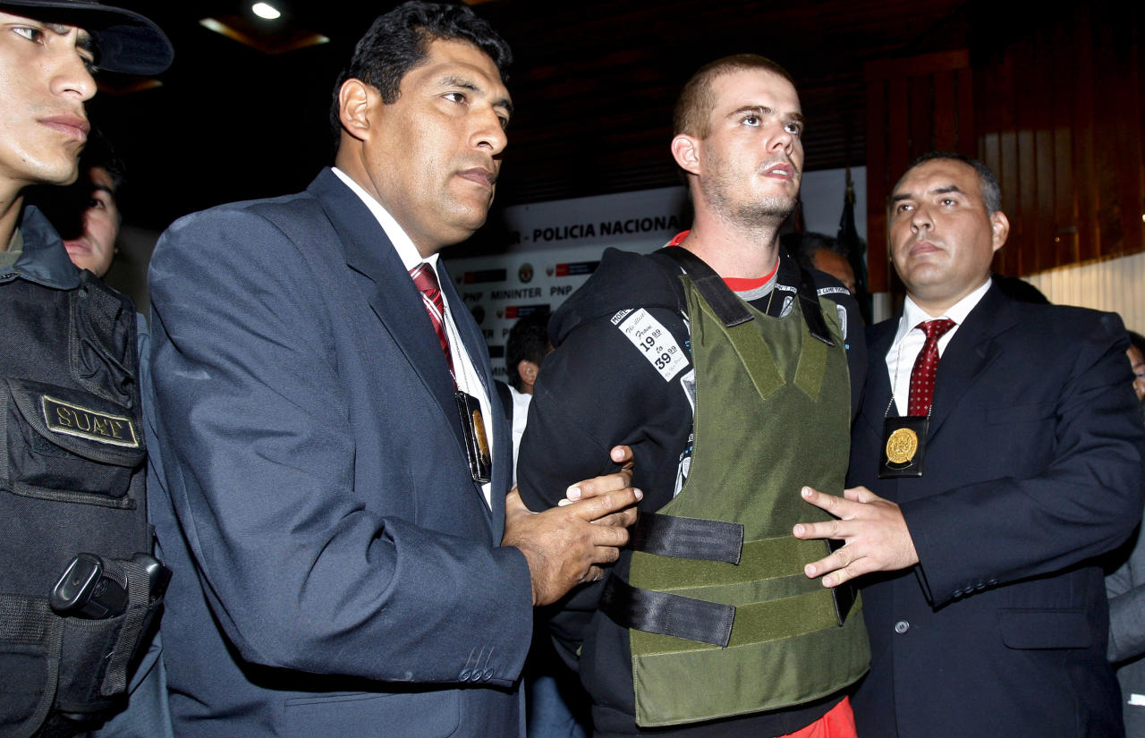 FILE in a June 5, 2010 file photo police officers escort Joran Van der Sloot, second right, during a press conference at a police station in Lima, Peru.   Peruvian police said Tuesday June 7, 2010 that Joran van der Sloot has confessed to killing a young woman in his Lima hotel room last week. (AP Photo/Karel Navarro/file)