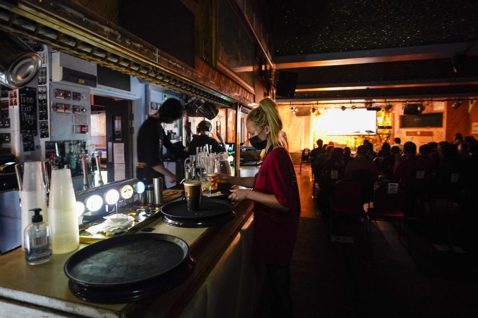 A waitress collects drinks whilst wearing a face mask at the Moth Club in Hackney, prior to their live show on stage, in London, Sunday, May 30, 2021. The return of live music in the city that produced bands from the Rolling Stones to the Spice Girls has reignited the creativity of some of London's many working artists after 14 months of silence. (AP Photo/Alberto Pezzali)