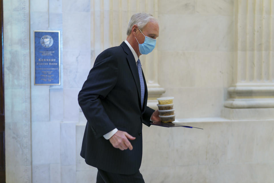 Sen. Ron Johnson, R-Wis., carries containers of food as he leaves a Senate Republican policy luncheon on Capitol Hill in Washington, Thursday, March 4, 2021. Johnson insisted that the entire text of the $1.9 trillion COVID relief bill be read aloud during its consideration. (AP Photo/J. Scott Applewhite)