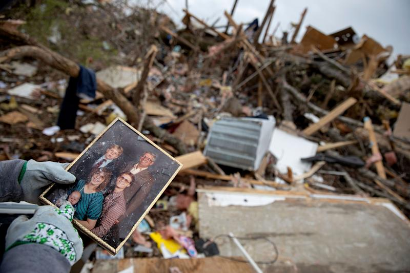 Danny Allen recovers a family photo while sifting through the debris of a friend's home destroyed by a tornado in Beauregard, Ala., March 4, 2019. (Photo: David Goldman/AP)