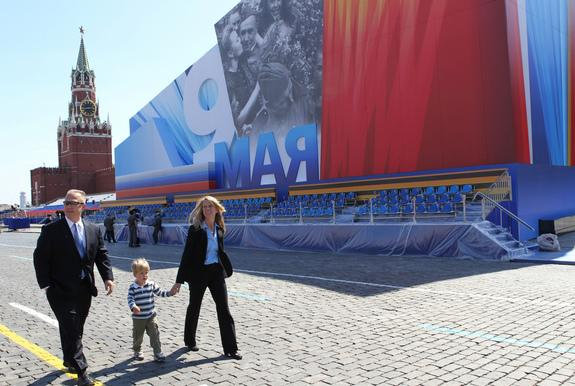 Expedition 36/37 Flight Engineer Karen Nyberg (right) takes a stroll through Red Square in Moscow in front of a grandstand and the Kremlin May 8 with her husband, astronaut Doug Hurley (left) and their 3-year-old son Jack. Nyberg, a NASA astron