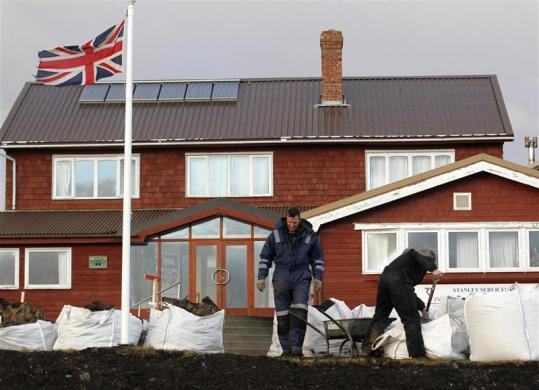 Workers clean the area of the Malvina Hotel in Stanley, Falkland Islands June 12, 2012.