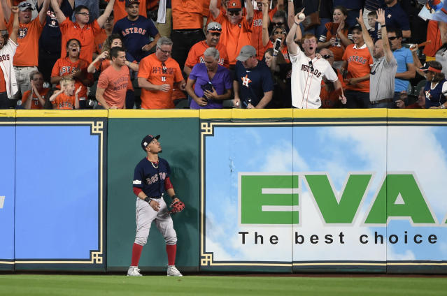 Boston Red Sox right fielder Mookie Betts watches as a fan holds a home run ball hit by Houston Astros' George Springer during the third inning in Game 2 of baseball's American League Division Series, on the bright side, Betts didn't have to try throwing this one back in. (AP Photo)