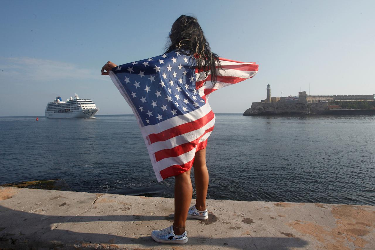 A woman with a U.S. flags looks at the arrival of U.S. Carnival cruise ship Adonia at the Havana bay, the first cruise liner to sail between the United States and Cuba since Cuba's 1959 revolution, Cuba, May 2, 2016. REUTERS/Stringer/File Photo              GLOBAL BUSINESS WEEK AHEAD PACKAGE Ð SEARCH ÒBUSINESS WEEK AHEAD SEPTEMBER 19Ó FOR ALL IMAGES