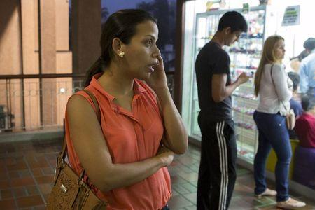 A woman talks on her phone in a mall in Caracas