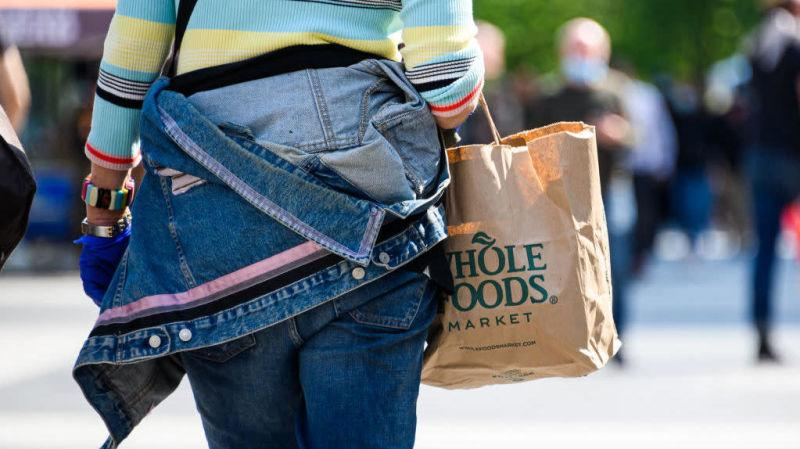 Person walking away from camera holding Whole Foods grocery bag
