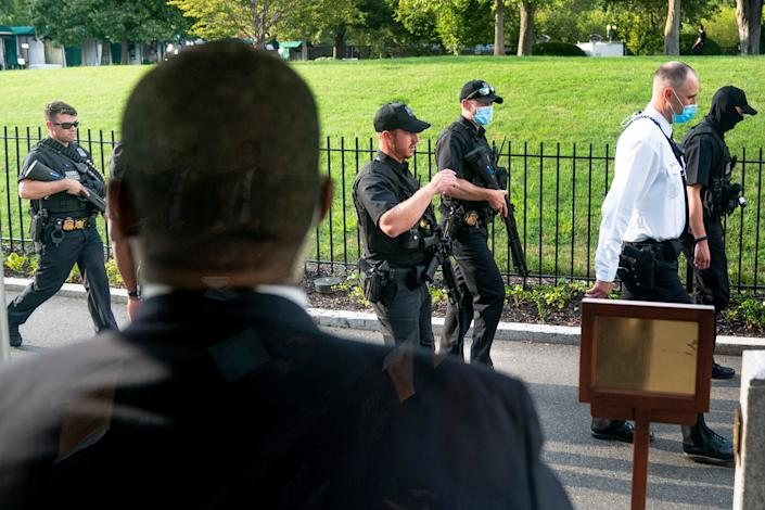 Members of the Secret Service stand guard outside the James Brady Press Briefing Room as President Donald Trump holds a news conference at the White House, Monday, Aug. 10, 2020, in Washington. Trump briefly left because of a security incident outside the fence of the White House.