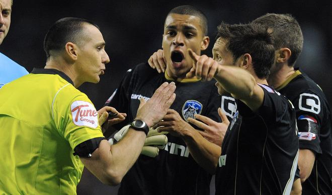 """Oldham Athletic's English midfielder Tom Adeyemi (3rd R) reacts next to the referee Neil Swarbrick (L) after hearing a supporter shouting towards him during the FA Cup football match between Liverpool and Oldham Athletic at Anfield in Liverpool, north-west England, on January 6 2012. Liverpool won the match 5-1.  AFP PHOTO / ANDREW YATES RESTRICTED TO EDITORIAL USE. No use with unauthorized audio, video, data, fixture lists, club/league logos or """"live"""" services. Online in-match use limited to 45 images, no video emulation. No use in betting, games or single club/league/player publications"""