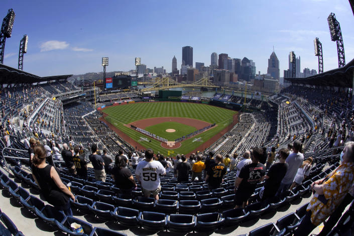 A limited number of baseball fans stand for the National Anthem before a baseball game, Thursday, April 8, 2021 between the Pittsburgh Pirates and the Chicago Cubs at PNC Park in Pittsburgh. (AP Photo/Gene J. Puskar)