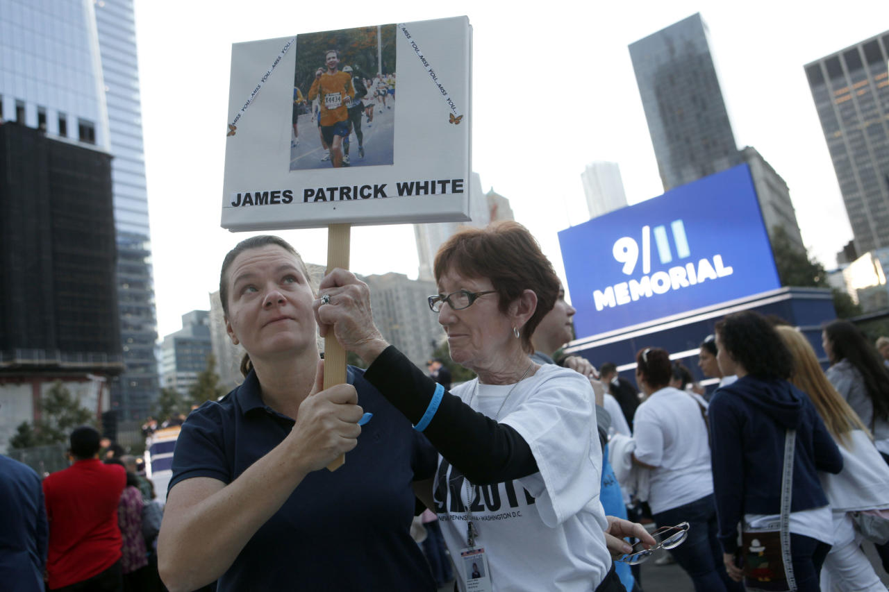 Rachel White, left, of Cherry Hill, N.J., and her aunt Dolores White, of Forest Hills, N.Y., hold aloft a sign memorializing Rachel's brother James Patrick White as friends and relatives of the victims of 9/11 gather for a ceremony marking the 10th anniversary of the attacks at the National September 11 Memorial at the World Trade Center site, Sunday, Sept. 11, 2011, in New York. (AP Photo/Jason DeCrow)