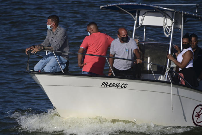 Jose Antonio Rodriguez, the father of 27-year-old Keishla Rodriguez, left, leaves the San Jose Lagoon after authorities found her remains there in San Juan, Puerto Rico, Saturday, May 1, 2021. A federal judge on Monday ordered Puerto Rican boxer Félix Verdejo held without bail after he was charged in the death of Rodriguez, his pregnant lover whose body was found in the lagoon. (AP Photo/Carlos Giusti)