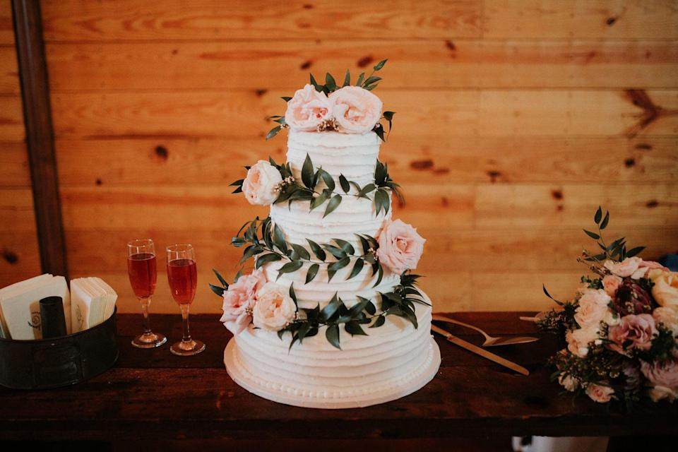 """<p>Draped in garland and <a href=""""https://www.fiftyflowers.com/"""" rel=""""nofollow noopener"""" target=""""_blank"""" data-ylk=""""slk:fresh flowers"""" class=""""link rapid-noclick-resp"""">fresh flowers</a>, this fall wedding cake would work for any time of year.</p>"""