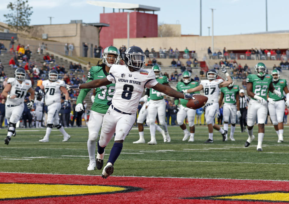 Utah State running back Gerold Bright (8) scores a touchdown ahead of North Texas defensive back Jameel Moore (39) during the first half of the New Mexico Bowl NCAA college football game in Albuquerque, N.M., Saturday, Dec. 15, 2018. (AP Photo/Andres Leighton)