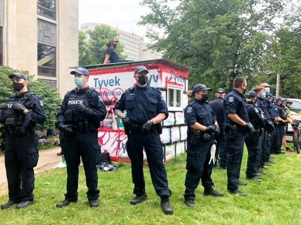 Halifax police surround a shelter on Aug. 18 outside the old library on Spring Garden Road to keep protesters back. One protestor sat on the shelter roof for hours to prevent its removal.  (Mark Crosby/CBC - image credit)