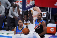 Denver Nuggets forward Will Barton (5) dunks in front of Oklahoma City Thunder forward Darius Bazley, left, and center Al Horford (42) during the second half of an NBA basketball game Saturday, Feb. 27, 2021, in Oklahoma City. (AP Photo/Sue Ogrocki)