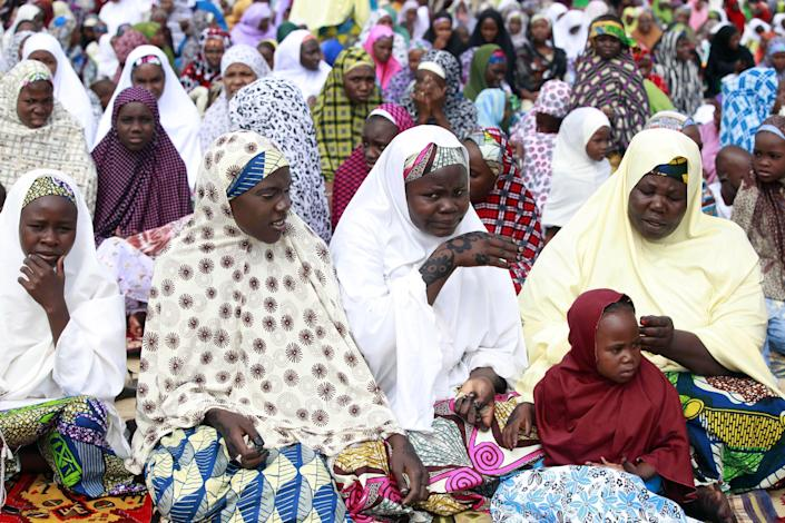 """Nigeria Muslim women and girls attend Eid al-Fitr prayers at Ramat square in Maiduguri, Nigeria, Thursday, Aug. 8, 2013. Nigerians in the birthplace of an Islamic uprising gripping the northeast Thursday celebrated the Muslim holy day of Eid al-Fitr with devout prayers and a joyful show of adulation for their king that attracted more than 10,000 people. It was the first durbar in three years in the city of Maiduguri and the joy that it could take place _ albeit amid massive security _ was heard in the cries of ululating women, screams of delight from children and men chanting """"Long live the king!"""" (AP Photo/Sunday Alamba)"""