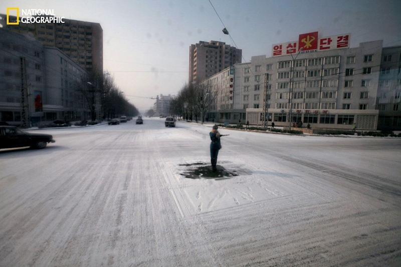 A traffic guard goes through the motions in the capital of Pyongyang, where streets are almost empty of cars. (David Guttenfelder/National Geographic)