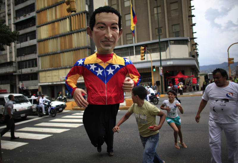 A person wearing a giant puppet depicting Venezuela's President Hugo Chavez crosses a street in downtown Caracas, Venezuela, Thursday, Sept. 27, 2012.  Venezuela's presidential election is scheduled for Oct. 7. (AP Photo/Ariana Cubillos)