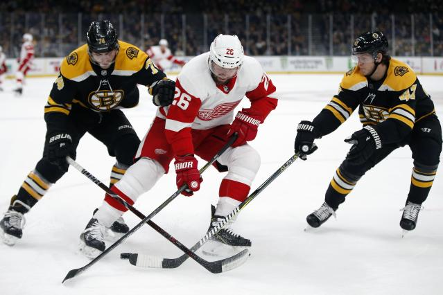 Detroit Red Wings' Thomas Vanek (26) battles Boston Bruins' Jake DeBrusk (74) and Torey Krug (47) for the puck during the first period of an NHL hockey game in Boston, Saturday, Dec. 1, 2018. (AP Photo/Michael Dwyer)