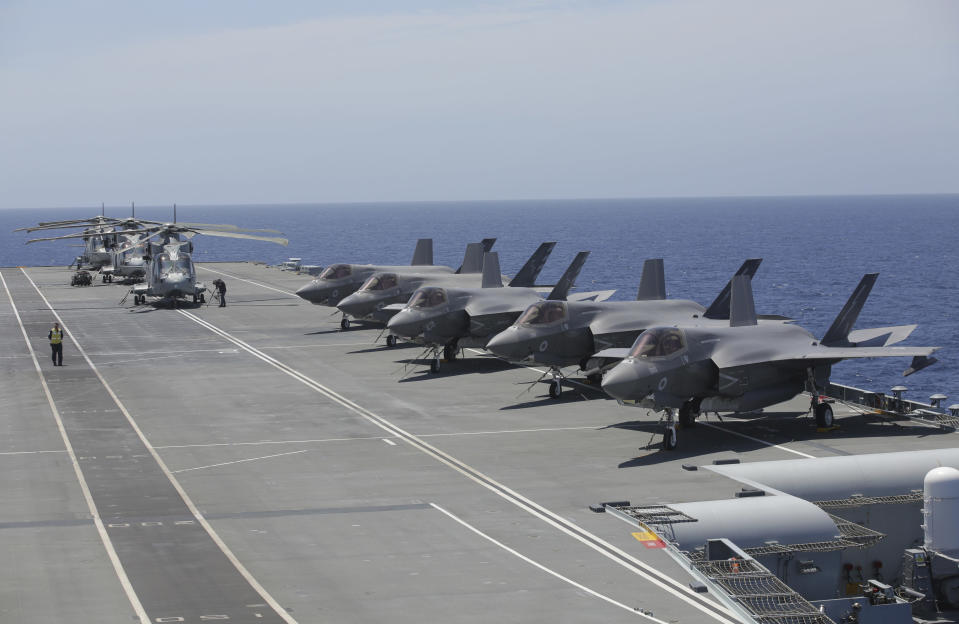 Military personnel inspect US and British jets as they participate in the NATO Steadfast Defender 2021 exercise on board the aircraft carrier HMS Queen Elizabeth off the coast of Portugal, Thursday, May 27, 2021. NATO has helped provide security in Afghanistan for almost two decades but the government and armed forces in the conflict-torn country are strong enough to stand on their own feet without international troops to back them, the head of the military organization said Thursday. (AP Photo/Ana Brigida)