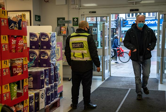 A security guard stands by the entrance to a Morrisons supermarket as a customer wearing a face mask enters the store (Getty)