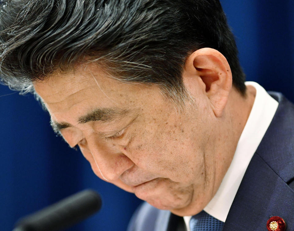 """Japanese Prime Minister Shinzo Abe downs his head as he says he is stepping down during a press conference at the prime minister official residence in Tokyo Friday, Aug. 28, 2020. Japan's longest-serving prime minister Abe said Friday he intends to step down because a chronic health problem has resurfaced. He told reporters that it was """"gut wrenching"""" to leave so many of his goals unfinished. (Kyodo News via AP)"""