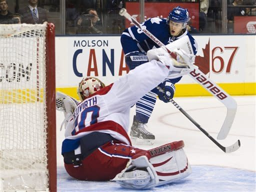 Washington Capitals goalie Michal Neuvirth, left, makes a glove-save on Toronto Maple Leafs forward Matt Frattin, back, during second-period NHL hockey game action in Toronto, Saturday, Feb. 25, 2012. (AP Photo/The Canadian Press, Nathan Denette)