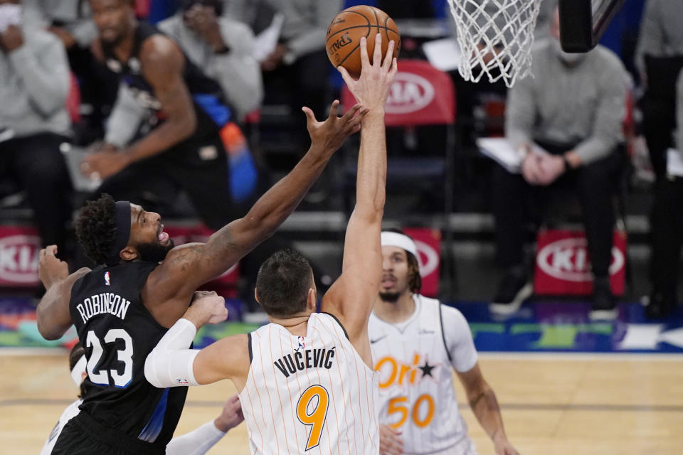 Orlando Magic center Nikola Vucevic (9) tips the ball away from New York Knicks center Mitchell Robinson (23) as Magic guard Cole Anthony (50) looks on during the first half of an NBA basketball game, Monday, Jan. 18, 2021, in New York. (AP Photo/Kathy Willens, Pool)