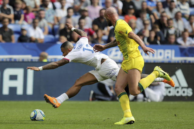Lyon's Memphis Depay, left, challenges for the ball with Nantes' Nicolas Pallois, right, during the French League 1 soccer match between Lyon and Nantes, at the Stade de Lyon in Decines, outside Lyon, France, Saturday, Sept. 28, 2019. (AP Photo/Laurent Cipriani)
