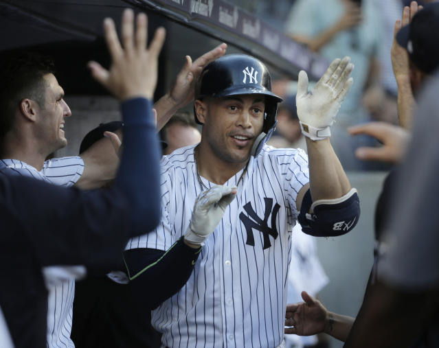 New York Yankees' Giancarlo Stanton is greeted by teammates after hitting a solo home run during the first inning of a baseball game against the Seattle Mariners at Yankee Stadium Tuesday, June 19, 2018, in New York. (AP Photo/Seth Wenig)