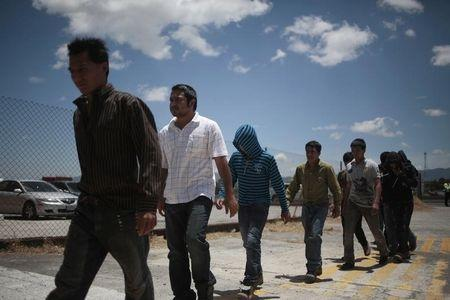 Illegal migrants from Guatemala, deported from Phoenix, Arizona in the U.S., walk after arriving at an air force base in Guatemala City