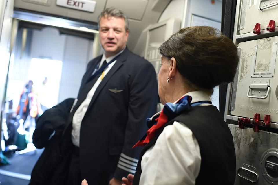 American Airlines longest serving flight attendant, Bette Nash (R), 81 years old, chats with the Captain before disembarking from her daily return flight to Boston at Ronald Reagan Washington Airport in Arlington, Virginia on December 19, 2017.   American Airlines Flight 2160 from Boston has just arrived in Washington, D.C., and Bette Nash, 81, helps the passengers disembark. After six decades crossing the skies as a flight attendant, Nash still has impeccable style, incredible energy and a constant smile. In the United States, pilots must retired at 65 but there is no such restriction on commercial flight attendants, of which Bette Nash is probably the world's most senior. / AFP PHOTO / Eric BARADAT        (Photo credit should read ERIC BARADAT/AFP via Getty Images)