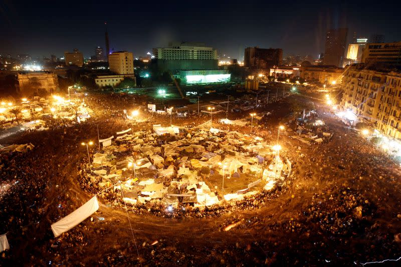 FILE PHOTO: Anti-government protesters in Cairo's Tahrir Square listen as President Hosni Mubarak speaks to the nation