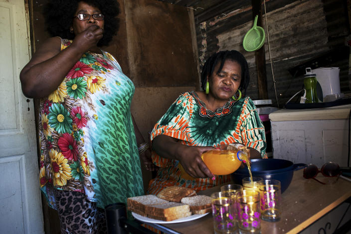 """<p>Grace, a resident of Khayelitsha, and her friend Angel, eating a meat dish and drinking a fruit-flavored drink with a high sugar content. When asked if she consumes fruit in her daily diet, she answers, """"Yes, I drink Coke and juice."""" In South Africa, approximately two-thirds of the population are overweight and women are affected more than men: 69.3 per cent of South African women have unhealthy levels of body fat and more than four in 10 are clinically obese. (Photograph by Silvia Landi) </p>"""