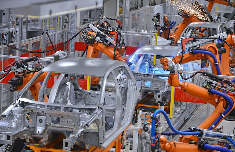Robotic arms assembling cars in a factory.