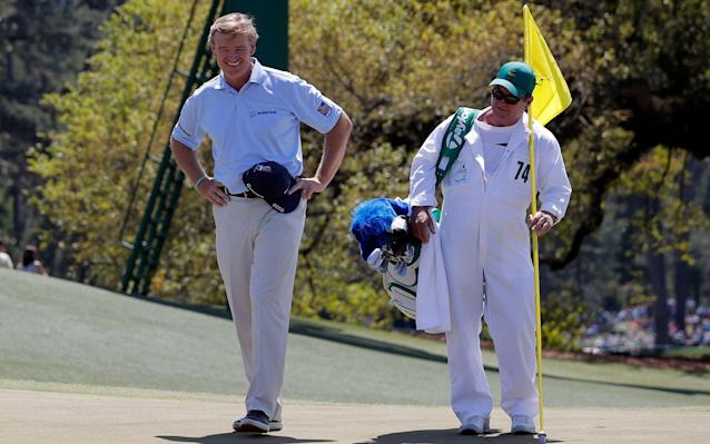 <span>Ernie Els of South Africa smiles as he finishes his round on the 18th hole with caddie Ricci Roberts in final round play during the 2017 Masters golf tournament at Augusta National</span> <span>Credit: JONATHAN ERNST/REUTERS </span>