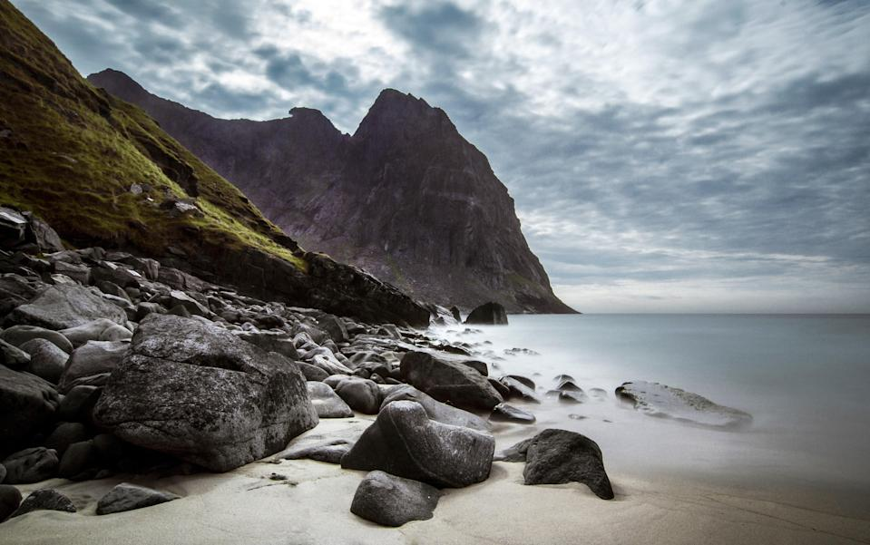 """If you want to really beat your friends at the beach game, we suggest visiting a stretch of sand above the Arctic Circle. The <a href=""""https://www.cntraveler.com/gallery/13-photos-that-will-make-you-want-to-visit-norways-lofoten-islands?mbid=synd_yahoo_rss"""" rel=""""nofollow noopener"""" target=""""_blank"""" data-ylk=""""slk:Lofoten Islands"""" class=""""link rapid-noclick-resp"""">Lofoten Islands</a>, an archipelago just off of Norway's northwestern coast, offer all the unique landscapes you could want, including the spectacular Kvalvika Beach. Found on the northern coast of Moskenes island, the beach's clear waters and stark views (courtesy of the surrounding vertical cliffs) will stop you right in your tracks. This isn't exactly the turquoise-water, sun-soaking beach Europe is known for... and that's exactly why we love it."""